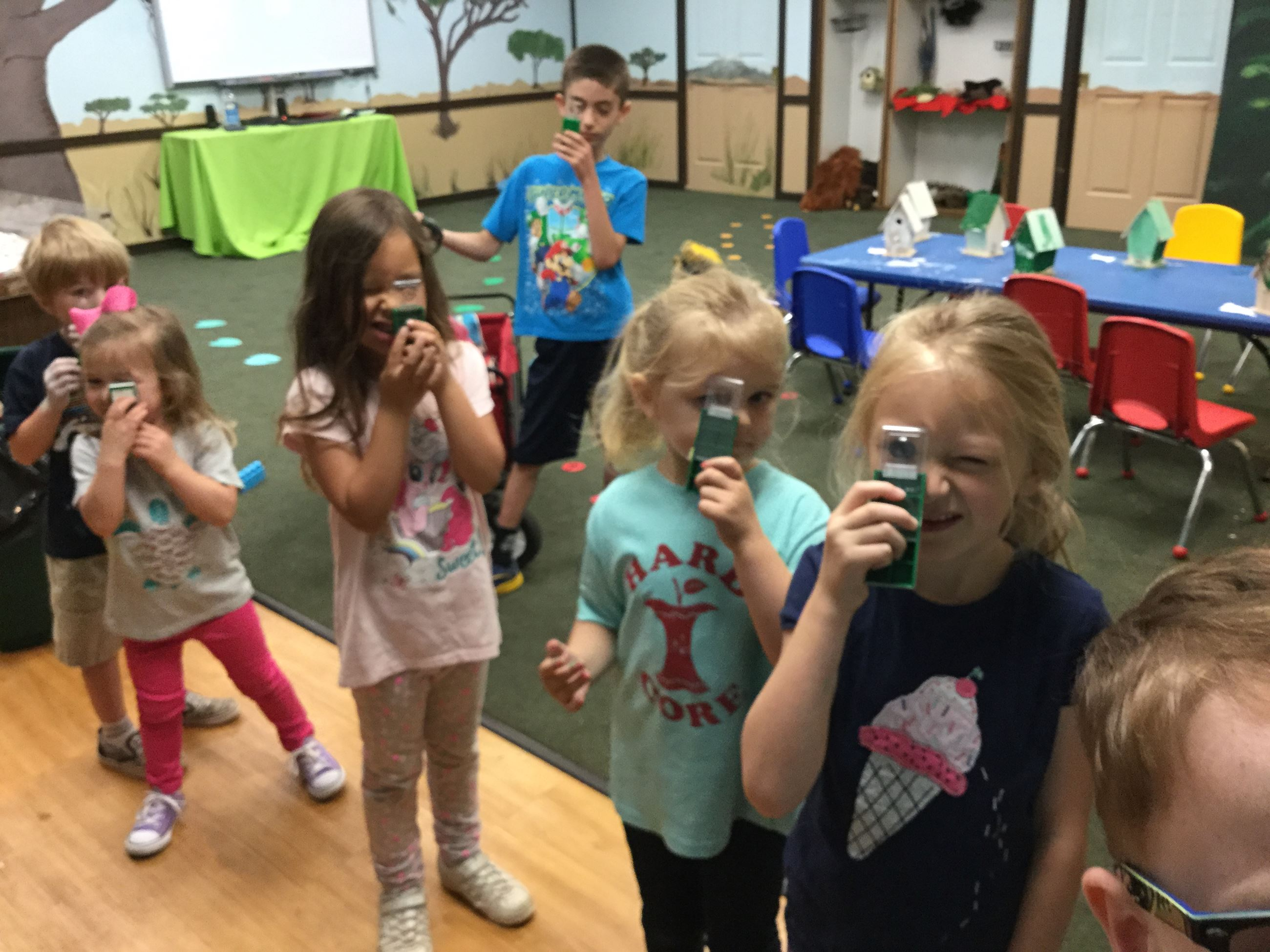 Young Children in a Classroom Playing with Magnifying Glasses